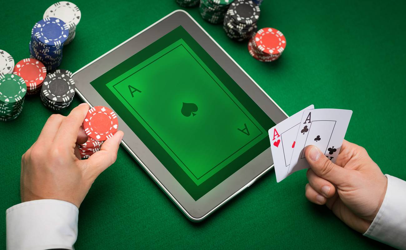 A person holding poker chips and cards playing blackjack in real life and  on tablet