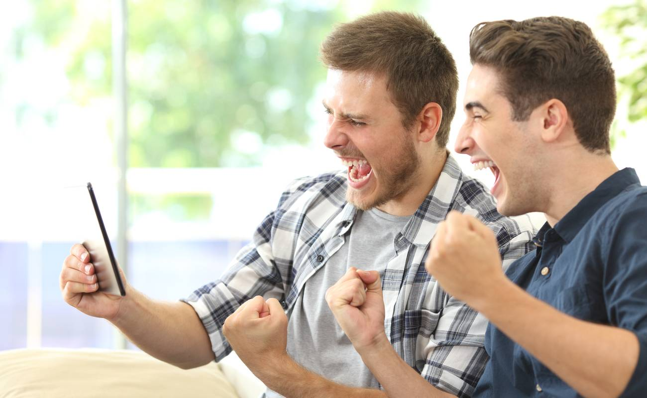 two men celebrating with their fists up whilst looking at a tablet