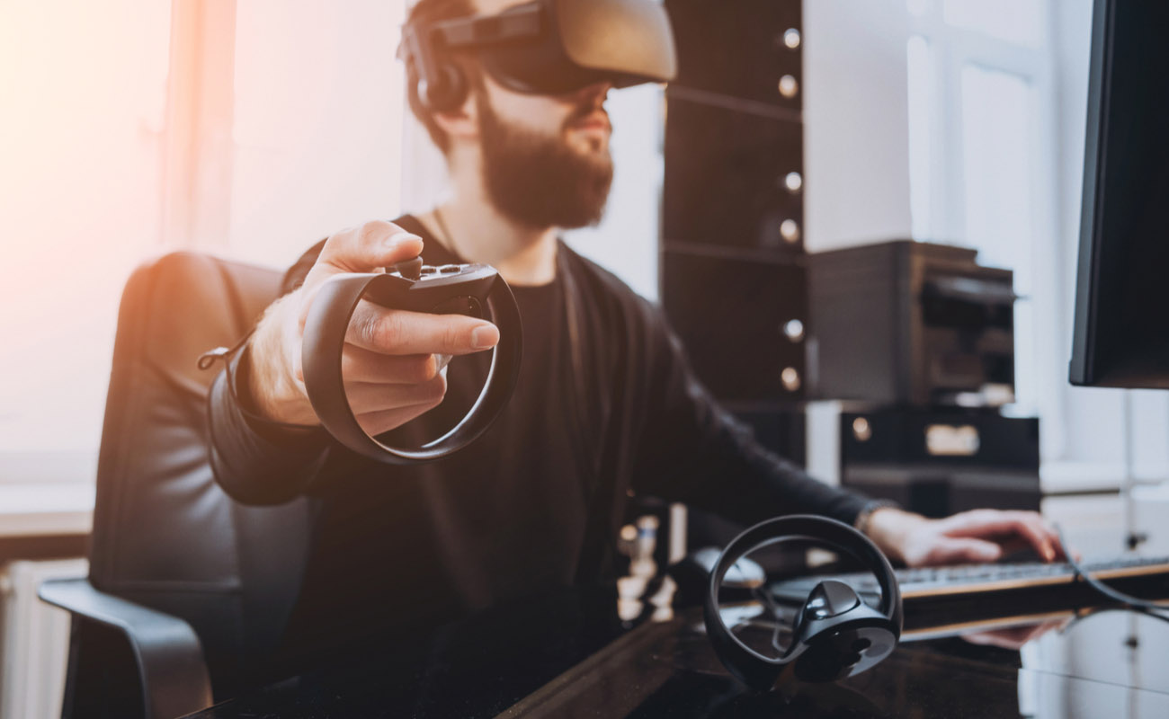 man playing virtual reality game with headset and consoles