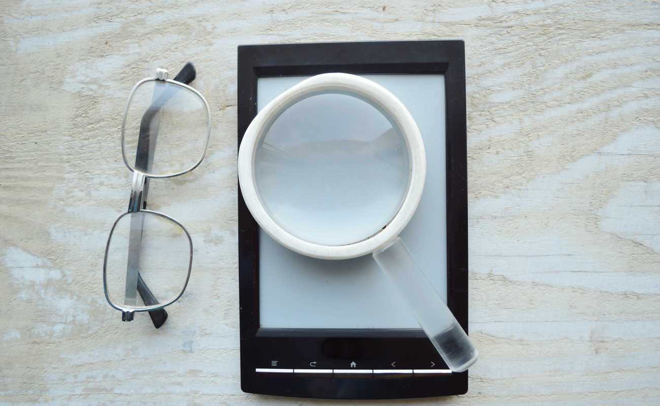 black ebook, reading glasses, notepad and magnifying glass
