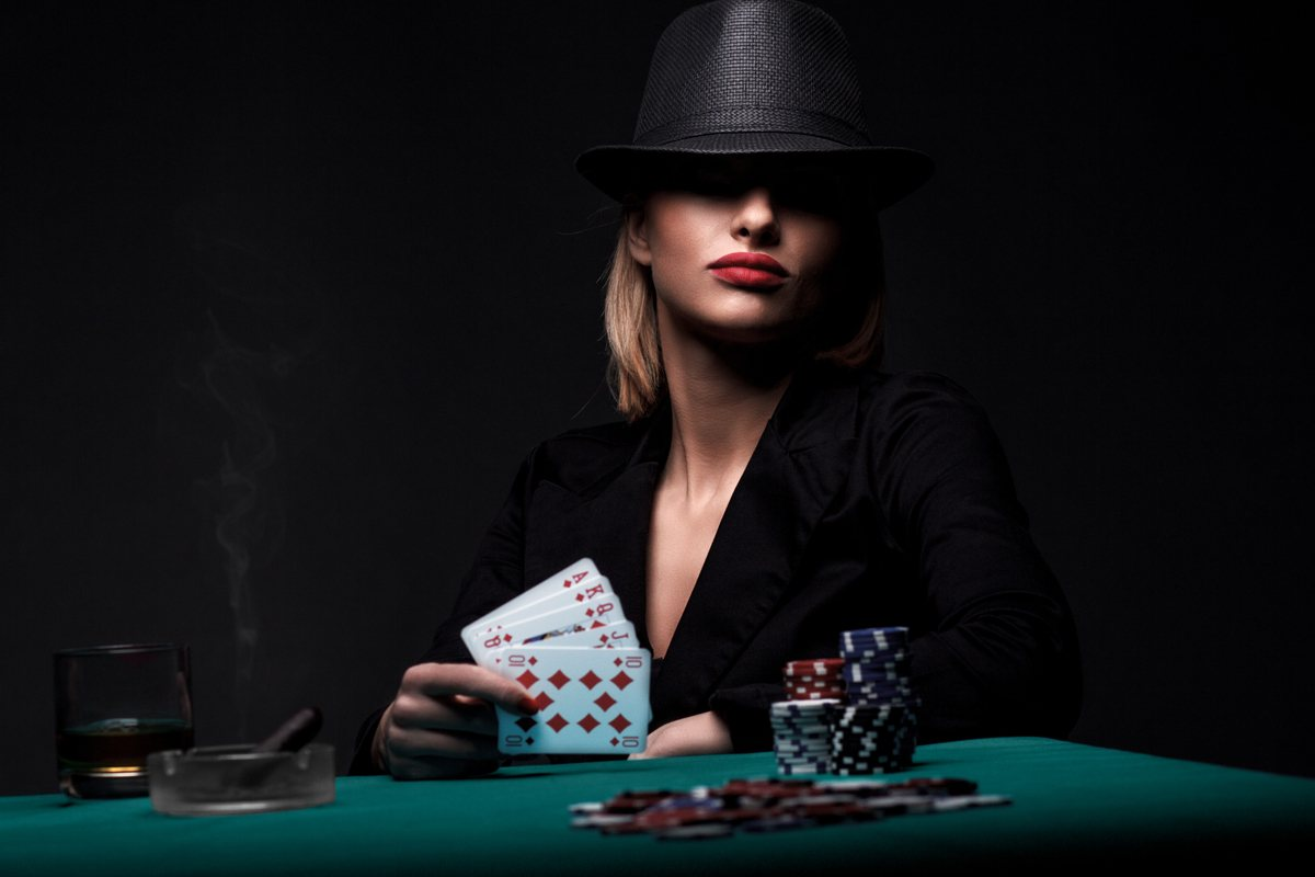 Woman wearing a black hat, holding a royal flush in her right hand