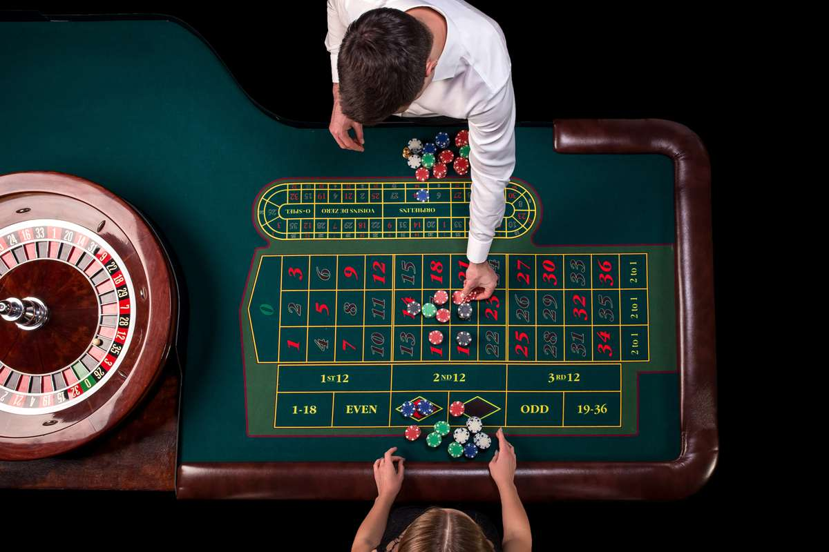 Male dealer handing out chips to a woman playing roulette on a green table