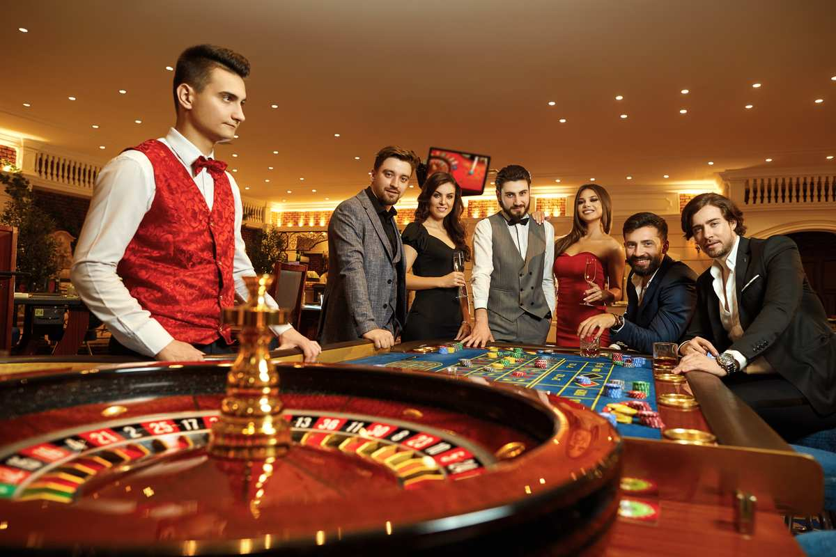 Group of friends playing roulette dressed up in suits and dresses