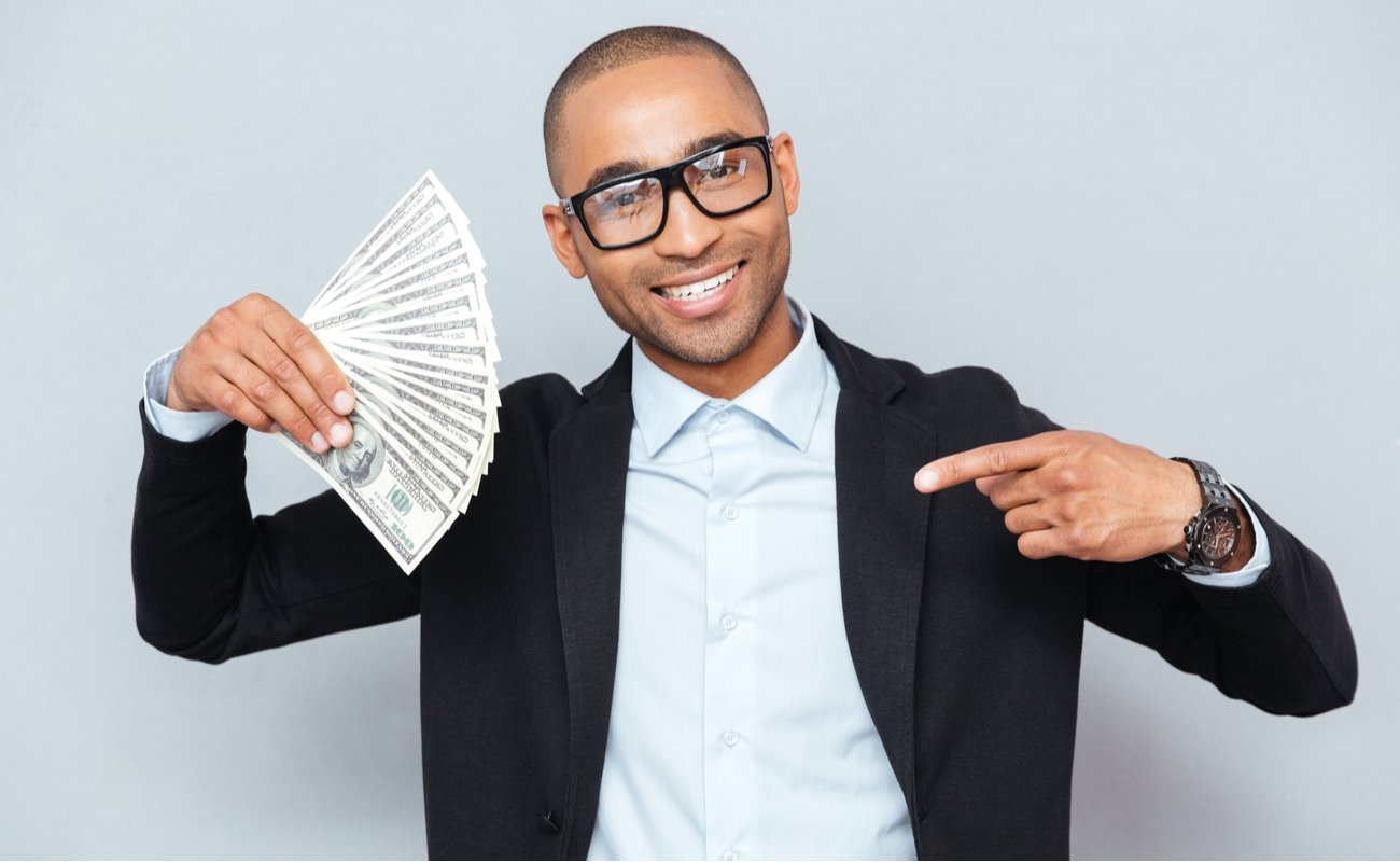 Happy young man holding dollars and pointing on it