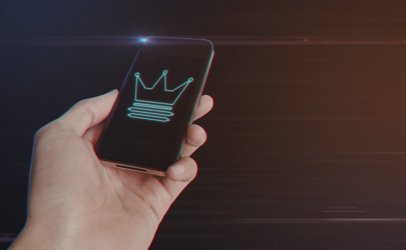 Close up of man hand holding a smartphone with Crown Icon