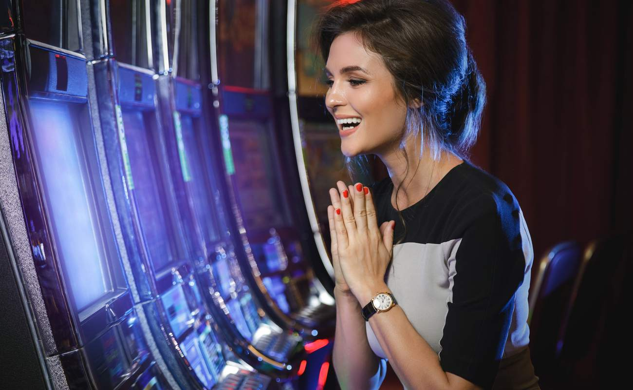Happy woman playing slot machines in the casino
