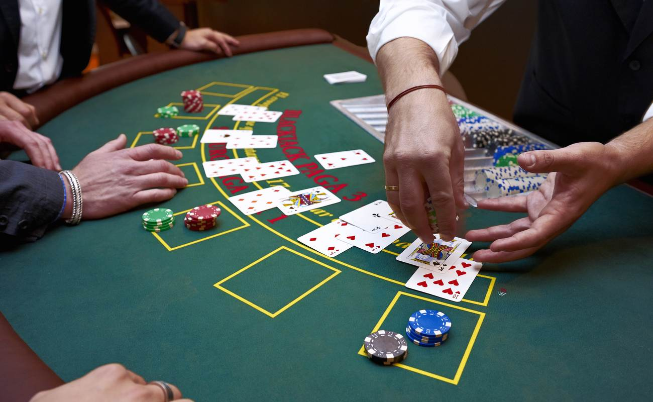 A close up of a blackjack dealer's hands in a casino, cards and chips