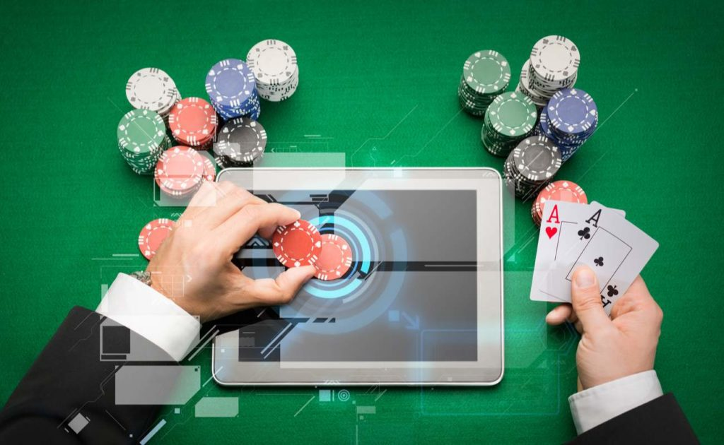 Close up of poker player with playing cards, tablet device and chips at green casino table