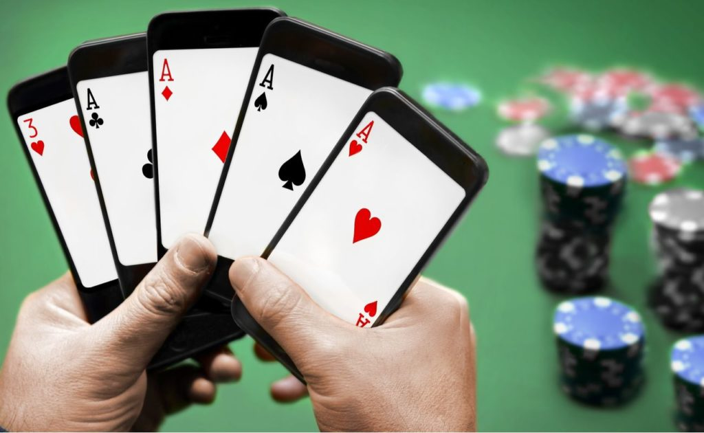Hands holding cellphones with cards on screen