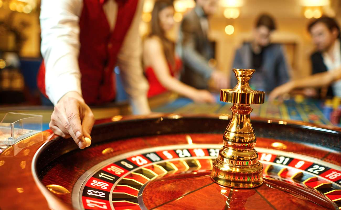 The croupier holds a roulette ball in a casino in his hand