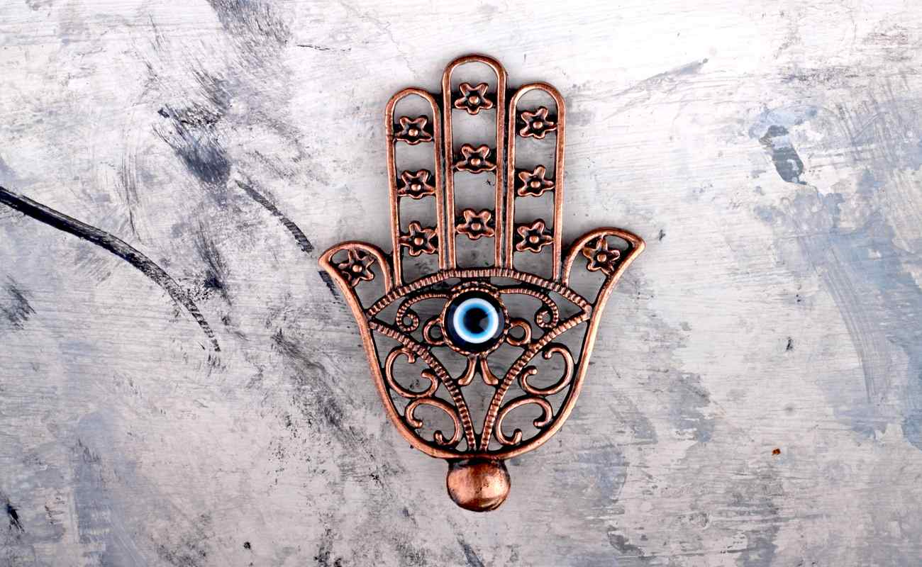 Golden Turkish Hamsa Hand Pendant with an evil eye bead in the center on concrete background