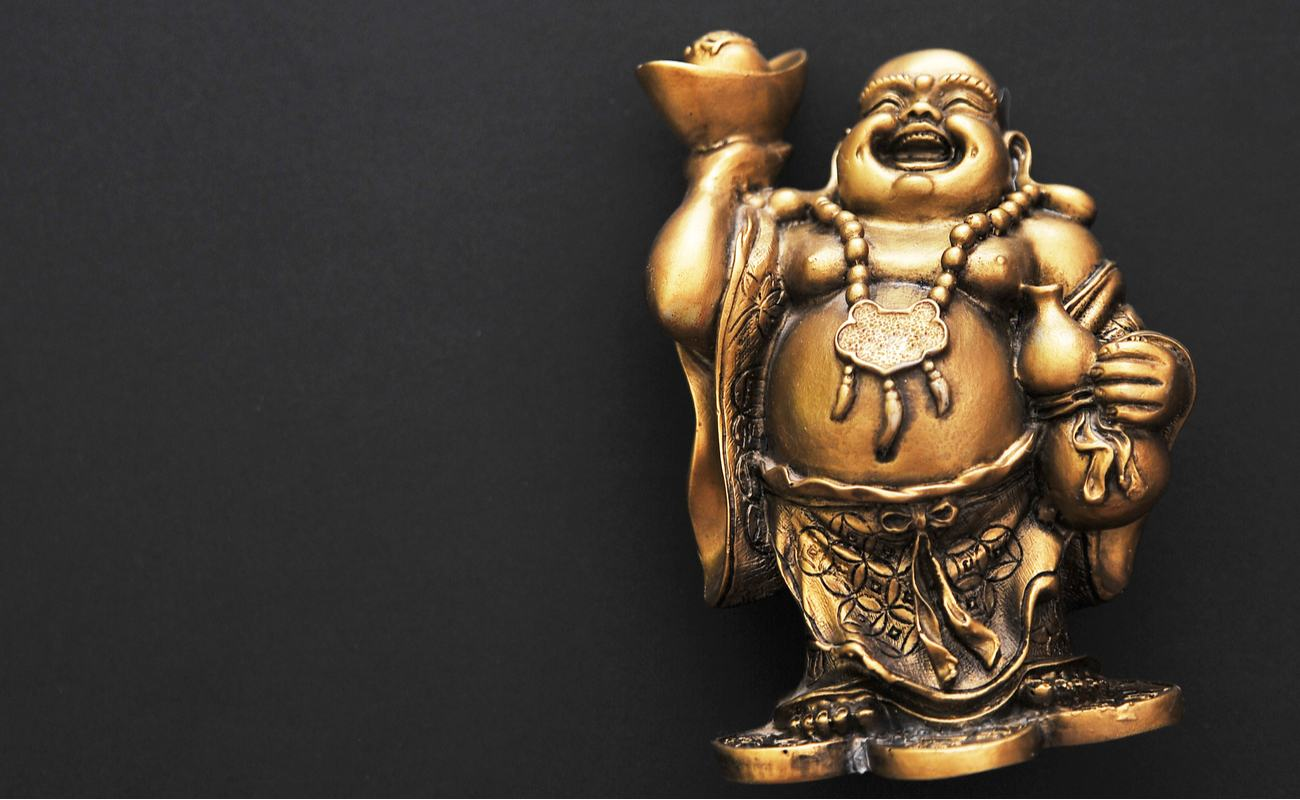 Golden laughing buddha statue on a black background