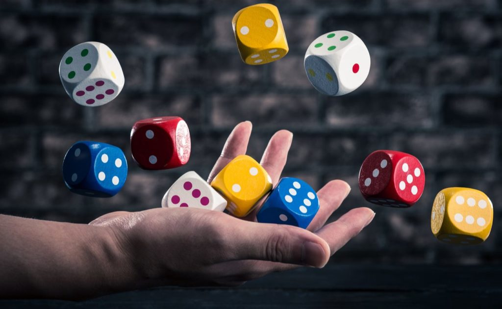 Multicolour dice thrown in the air by hand
