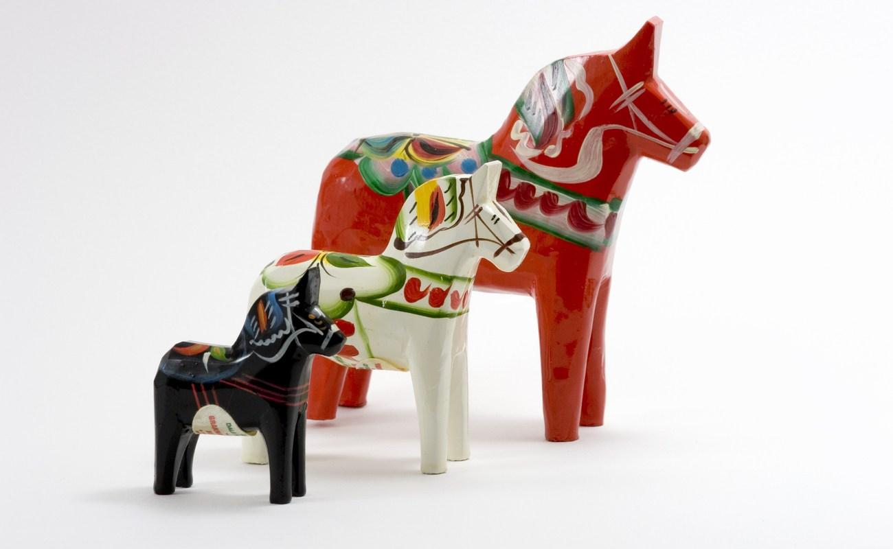 Three Swedish Dala Horses lined up on a white background
