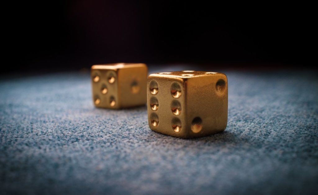 Closeup of lucky golden gambling dice on billiards table