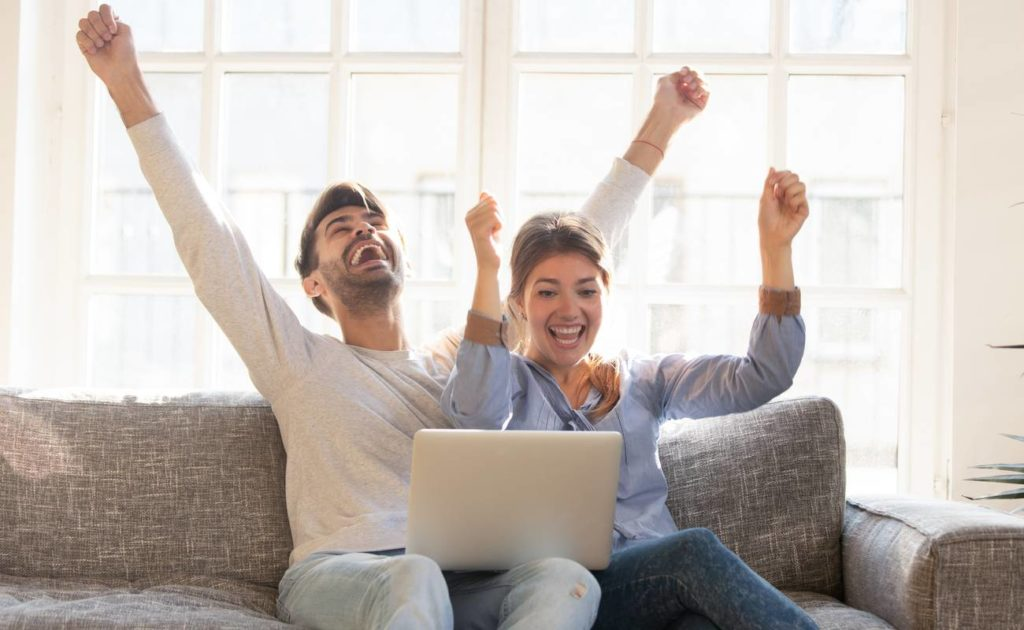 Happy young couple celebrate online victory, screaming with joy raising hands