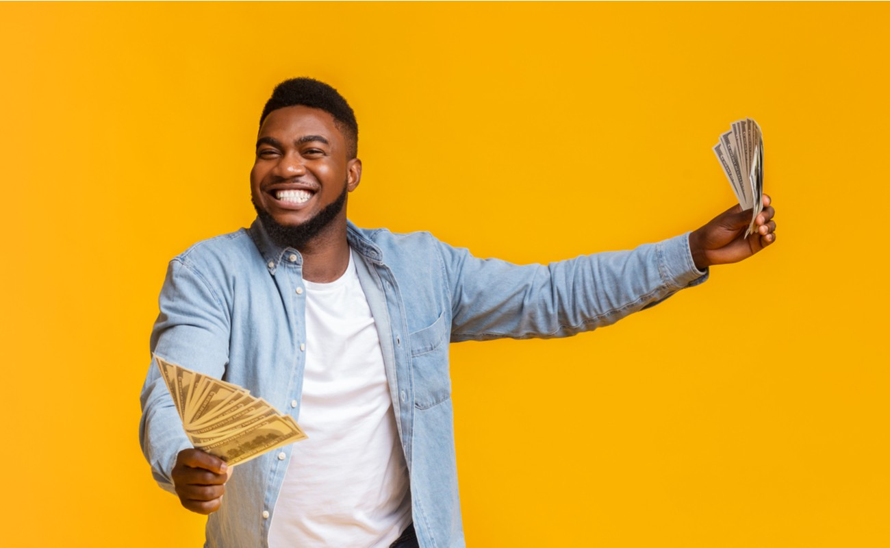 Overjoyed Man Holding Money In Both Hands On Yellow Background