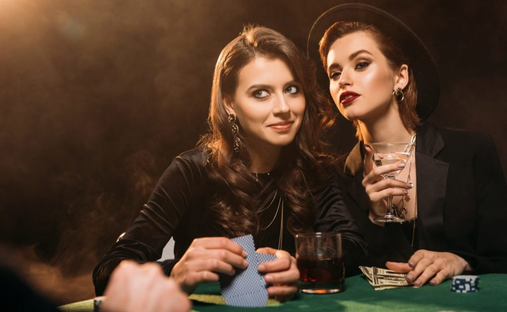 Two beautiful women playing poker at a table in a casino
