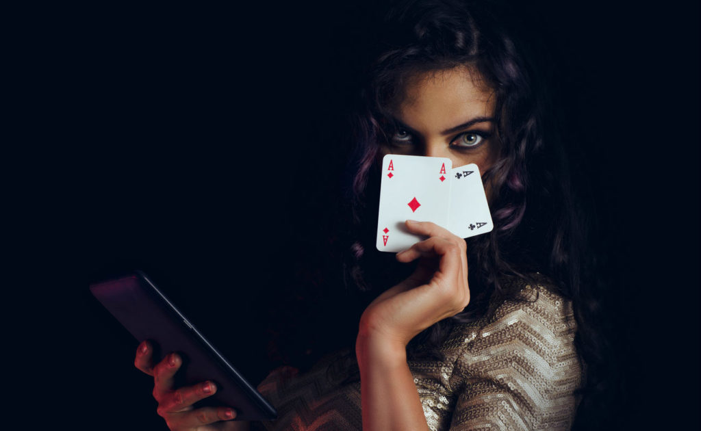 Mystic beautiful girl, covering face with cards and holding tablet in hand