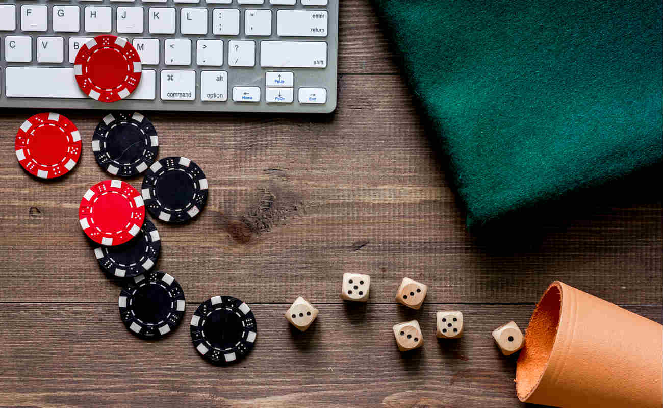 Online poker. Chips and the dice nearby keyboard on wooden table top view copyspace