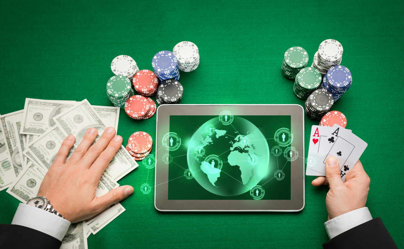 poker player holding playing cards, chips and earth projection with users icons on tablet pc