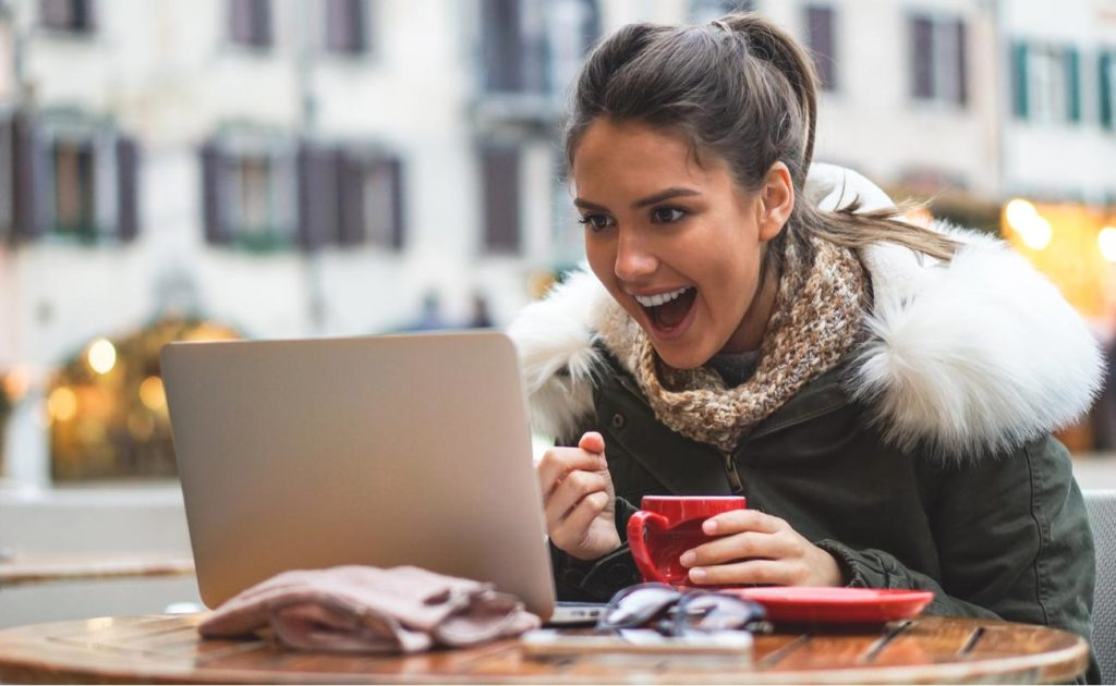 woman on her computer in a bar in city center drinks coffee while shopping online