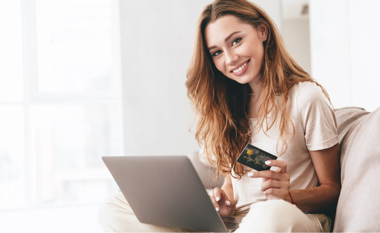 smiling woman showing credit card to the camera while on laptop