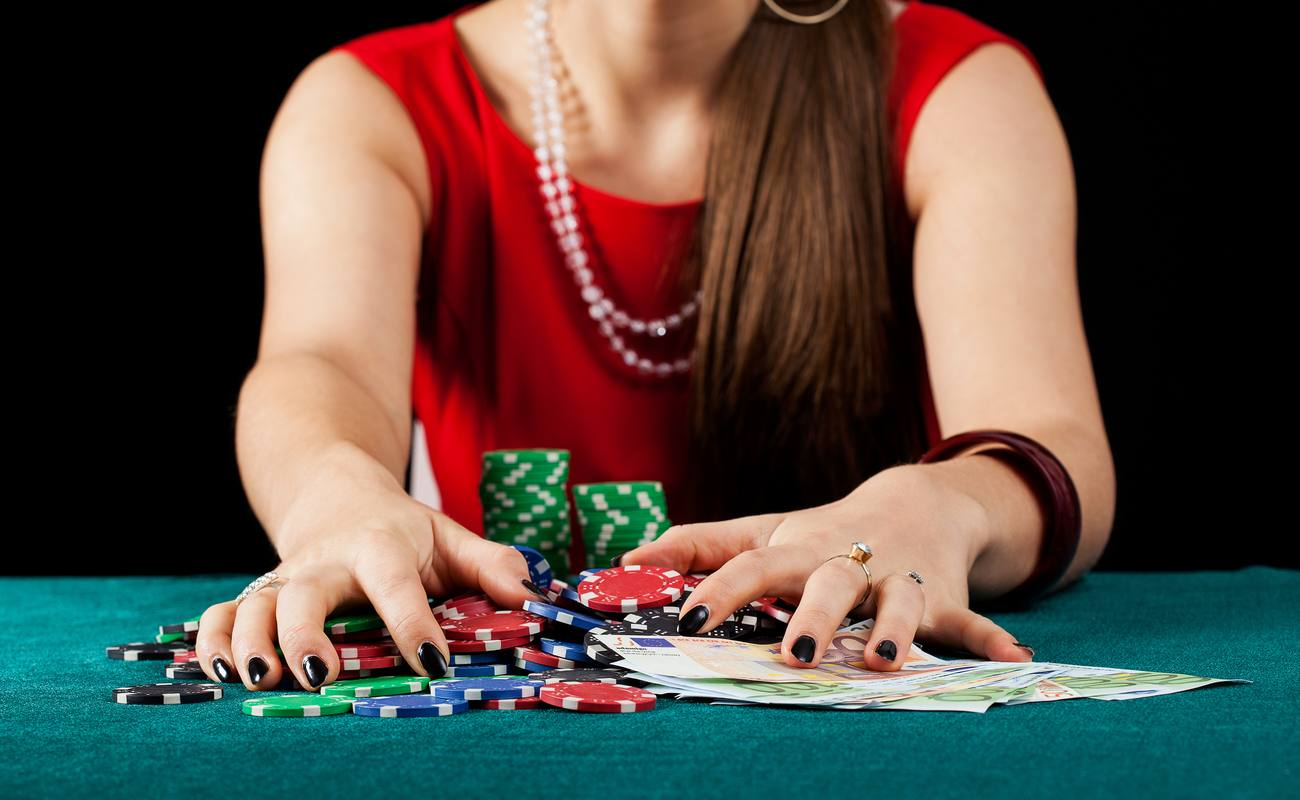 An elegant female gambler taking chips and banknotes