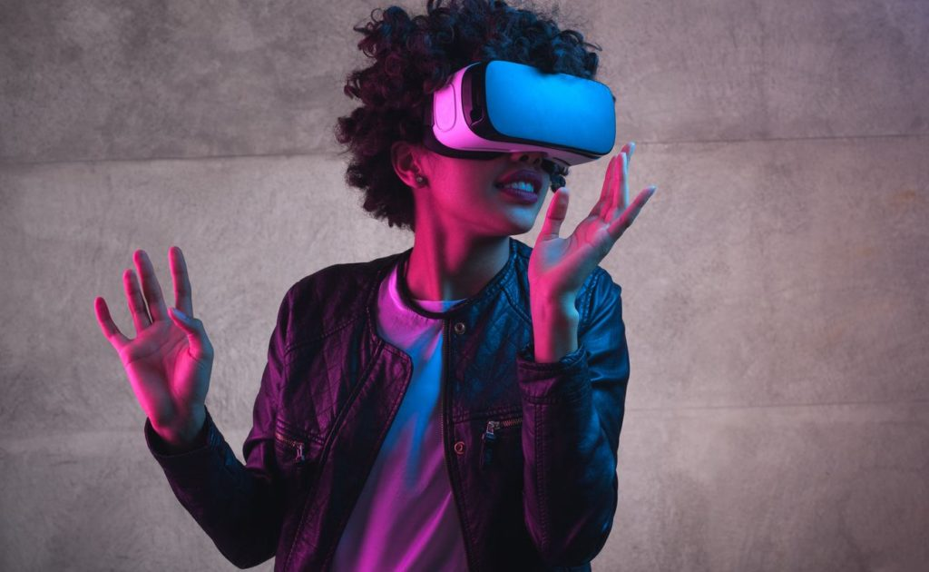 Cheerful girl with hands up wearing virtual reality goggles.