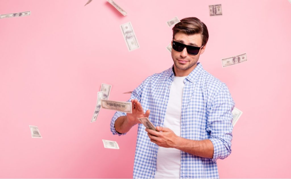 Portrait of trendy carefree man surrounded by money isolated over pink pastel background