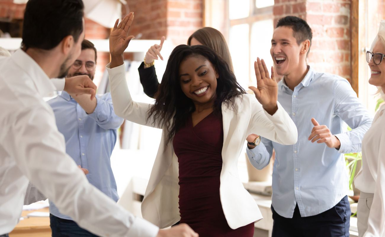 Happy businesswoman with coworkers enjoying victory dance