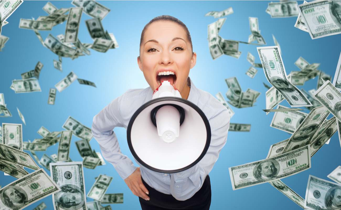 Businesswoman with megaphone and money rain falling against blue background