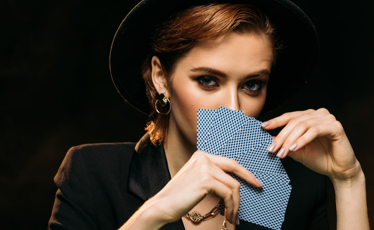 Attractive woman in jacket and hat covering face with poker cards isolated on black background