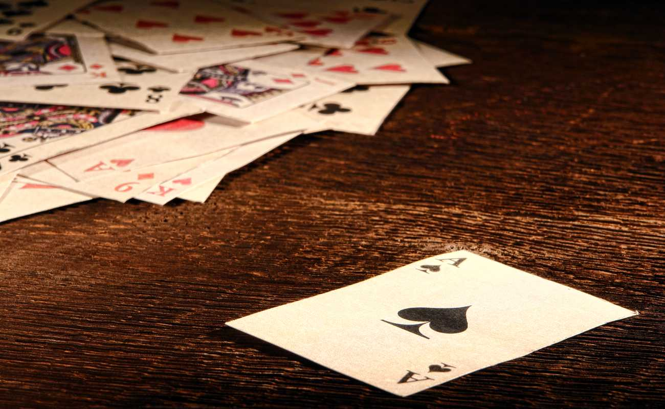 Ace Of Spades playing card and stack of antique poker game cards on wooden table