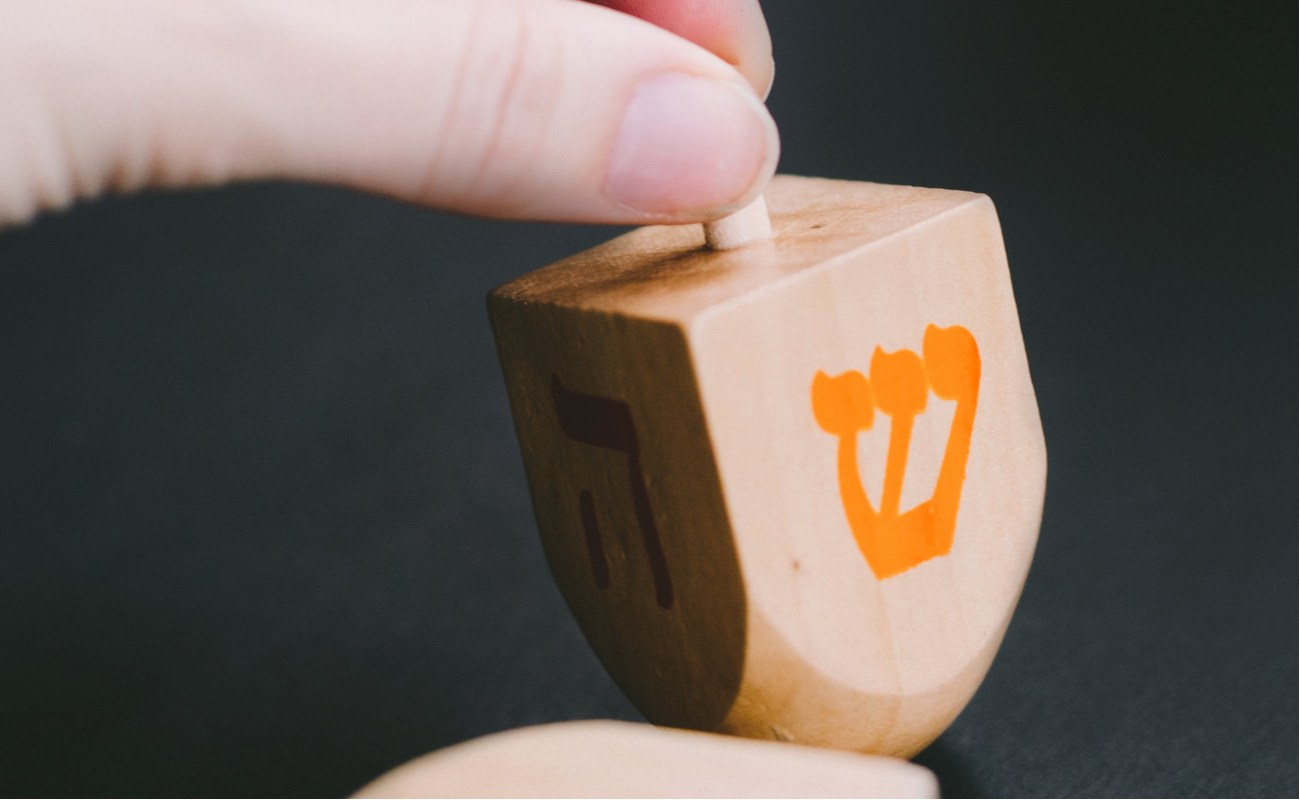 """A Dreidel in hand with the """"shin"""" character facing out before being spun"""