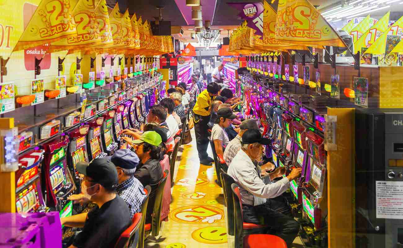 Pachinko game center with rows of people playing