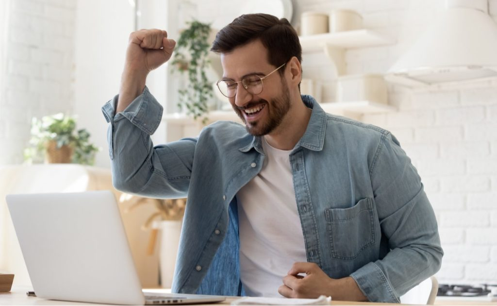 Excited young man on laptop at table celebrating online success