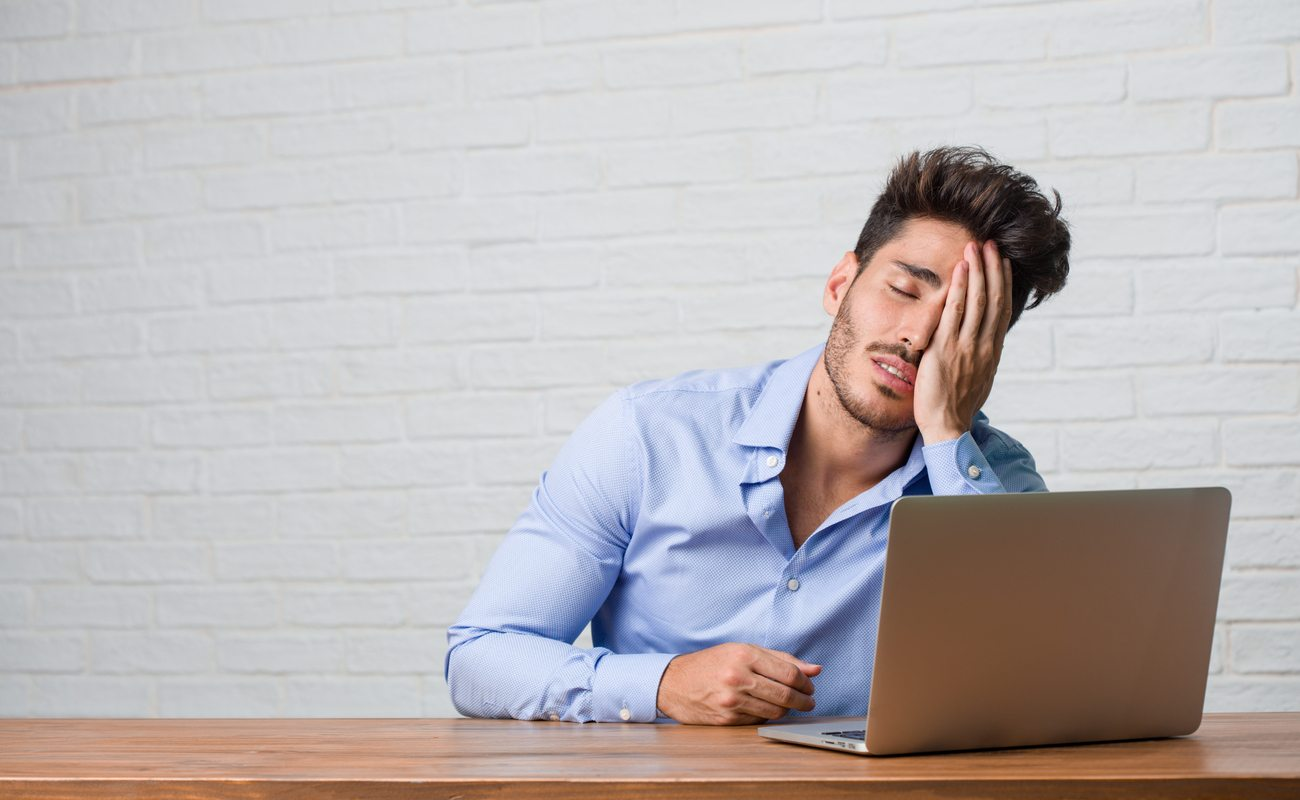 Young businessman sitting at laptop frustrated