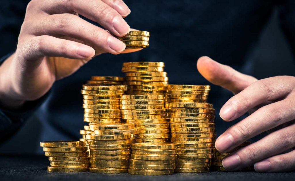 Golden coins stacked between hands