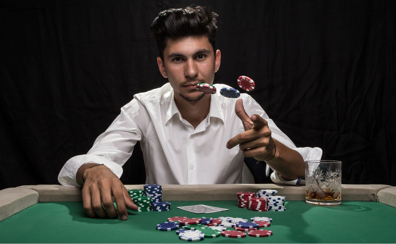 Man sitting at poker table while throwing chips