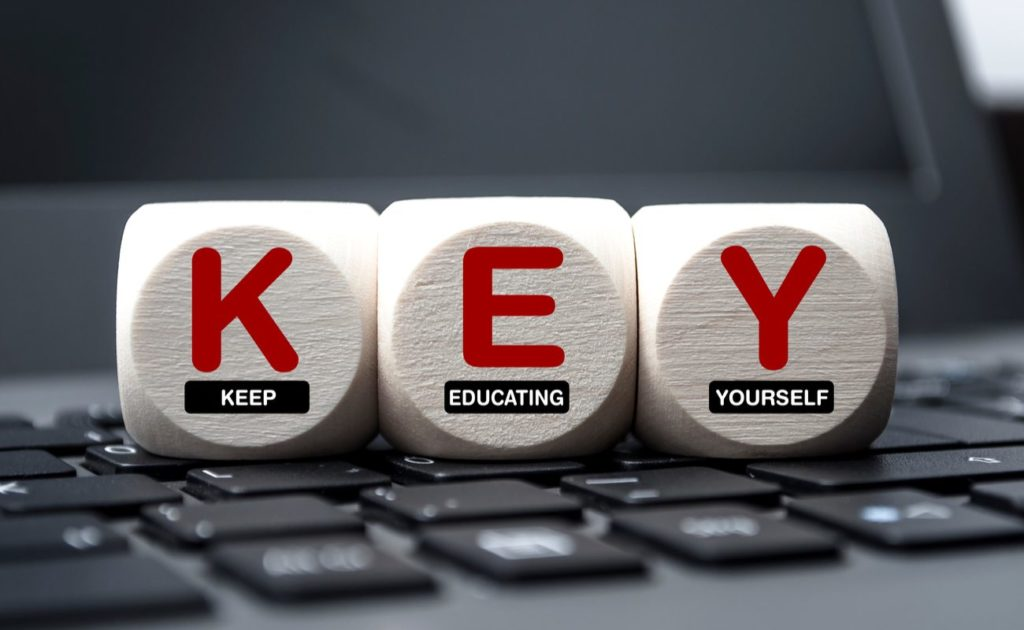 Cubes dice on keyboard with the words KEY Keep Educating Yourself