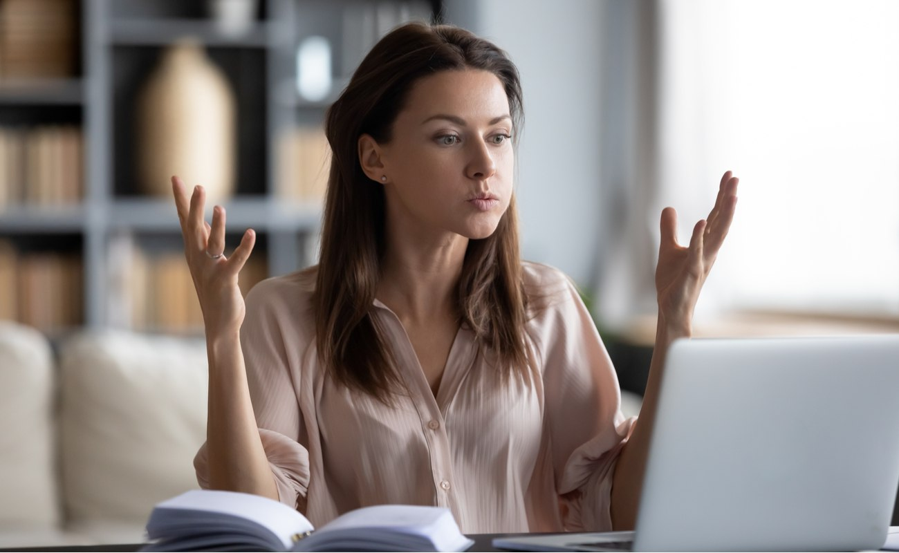 Irritated young woman looking at laptop screen