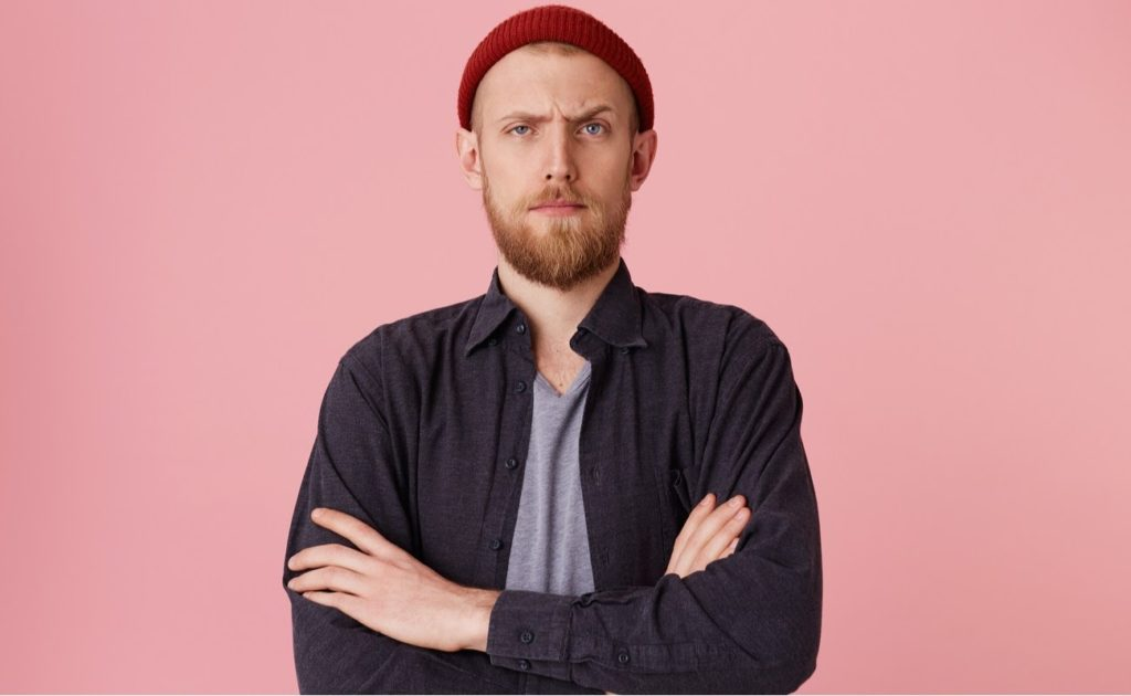 Close up of bearded man standing in front of pink background, looking at the camera with one raised eyebrow