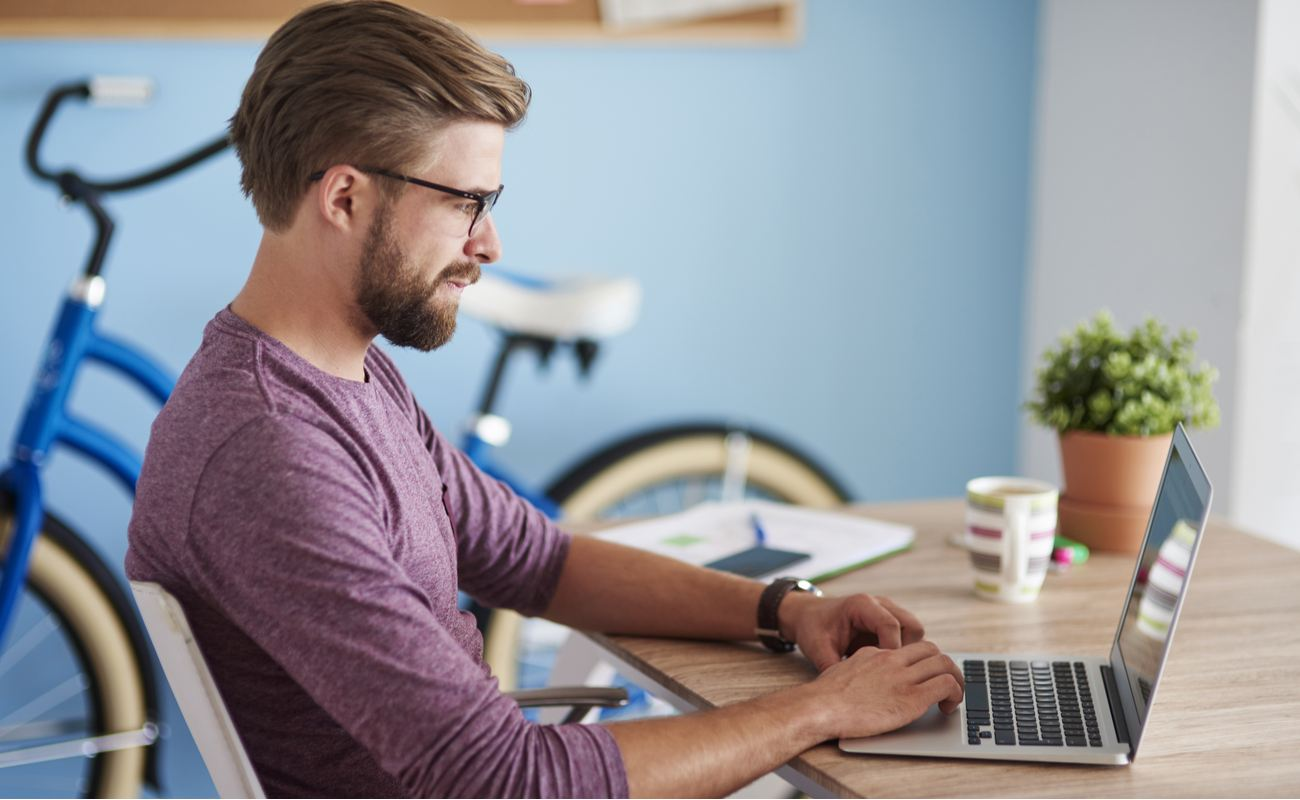 Hipster man playing on laptop at home with bicycle in background