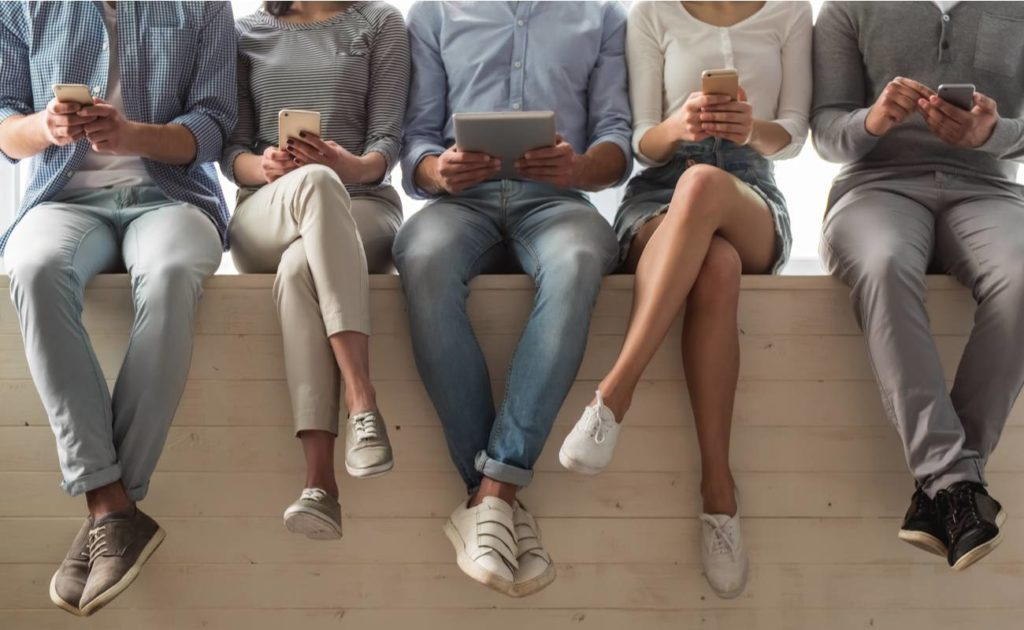 Row of people sitting on the wall with smartphones and tablets in their hands