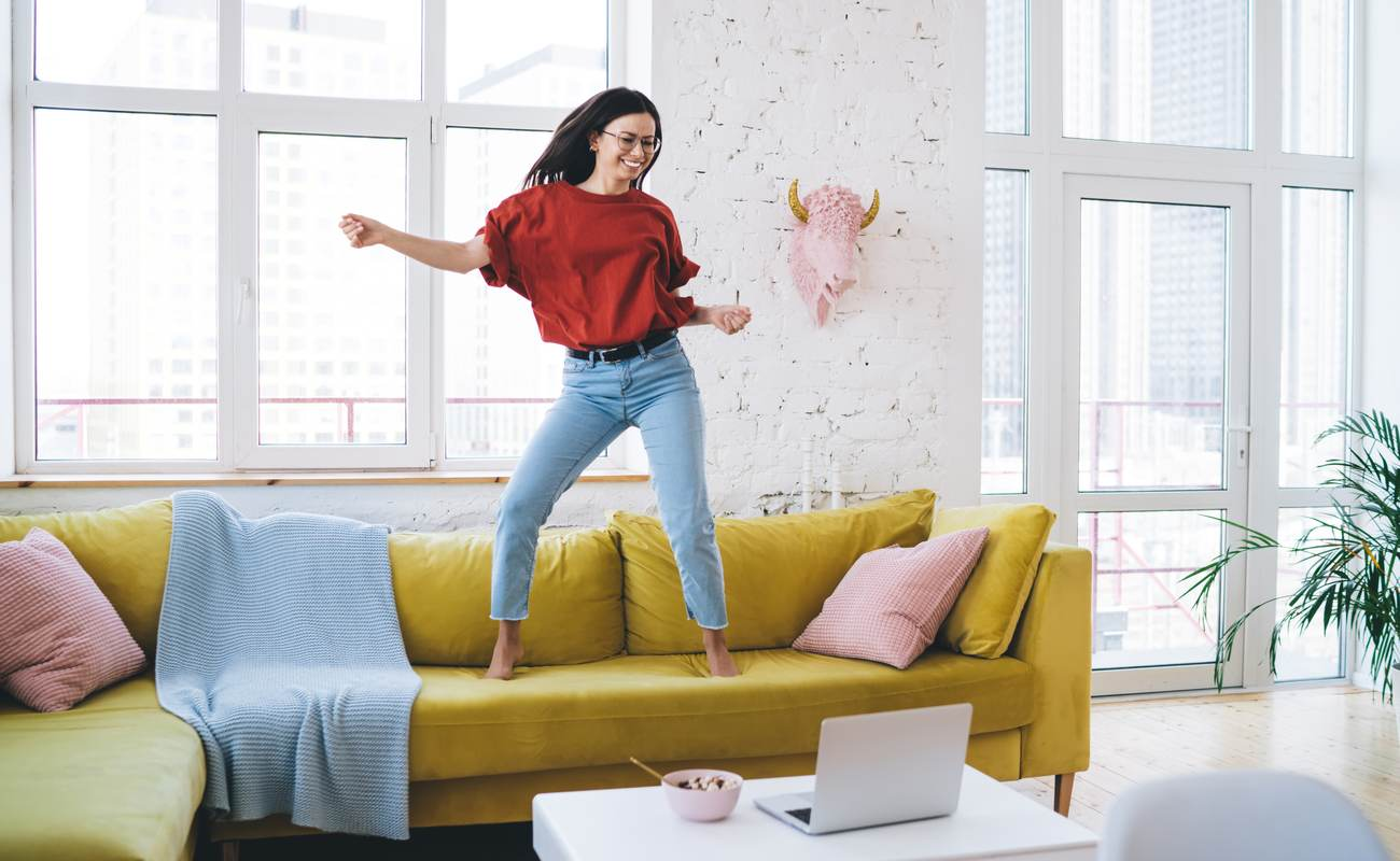 Young joyful woman dancing on yellow couch in living room near coffee table with laptop