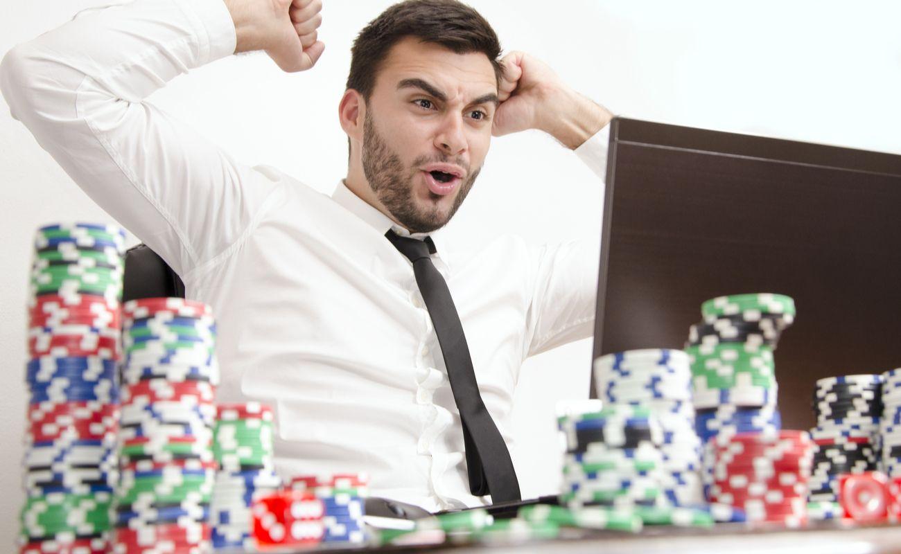 Pria menunjukkan kegembiraan saat melihat laptop dengan chip poker di atas meja