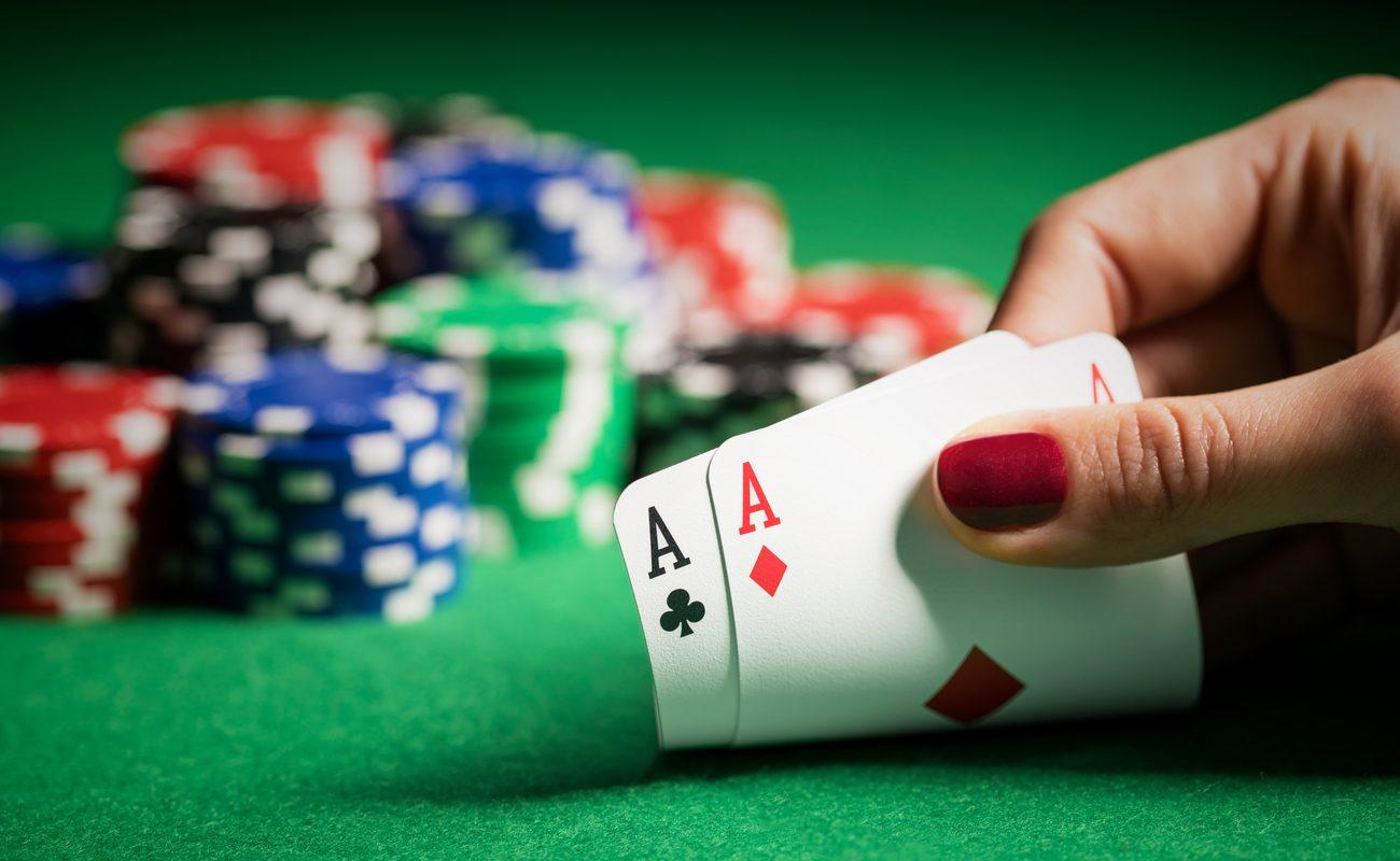 Tangan memegang dua kartu as di atas meja poker dengan chip poker