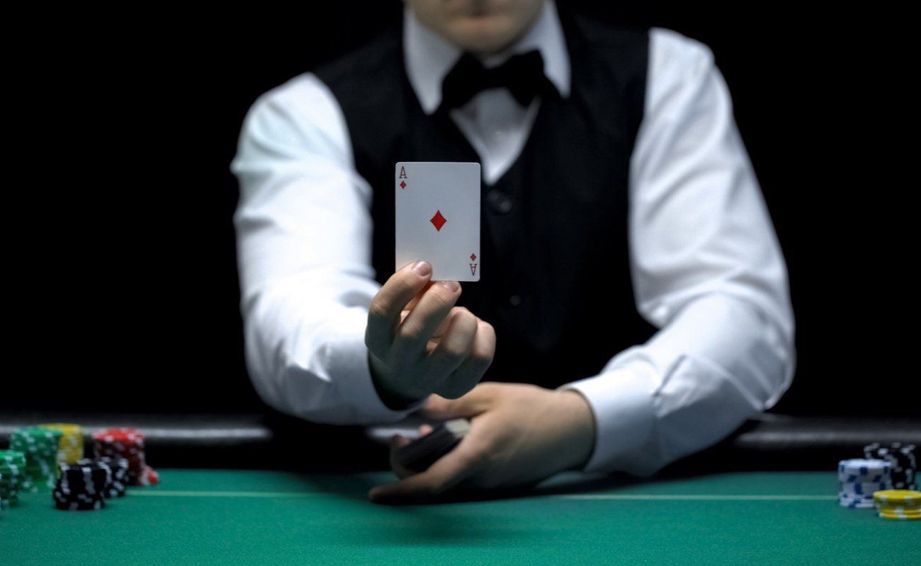 Casino dealer shows an ace card in front of the camera.
