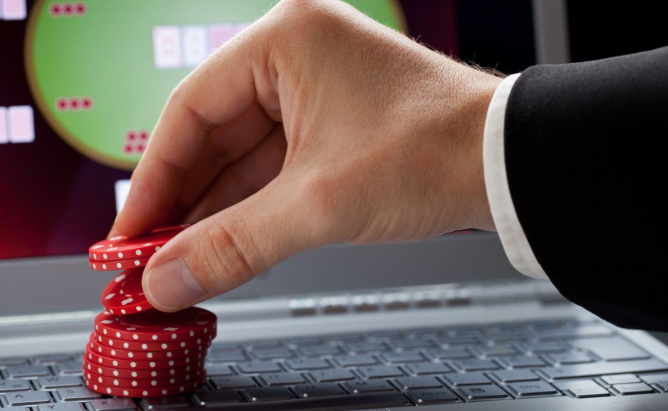 Pemain menempatkan chip pada laptop yang menunjukkan kasino online